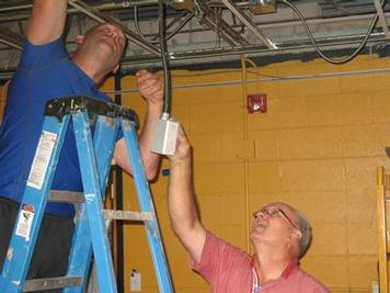 Boosters Roger Grenoble and Scott Stykel work on the new concession stand